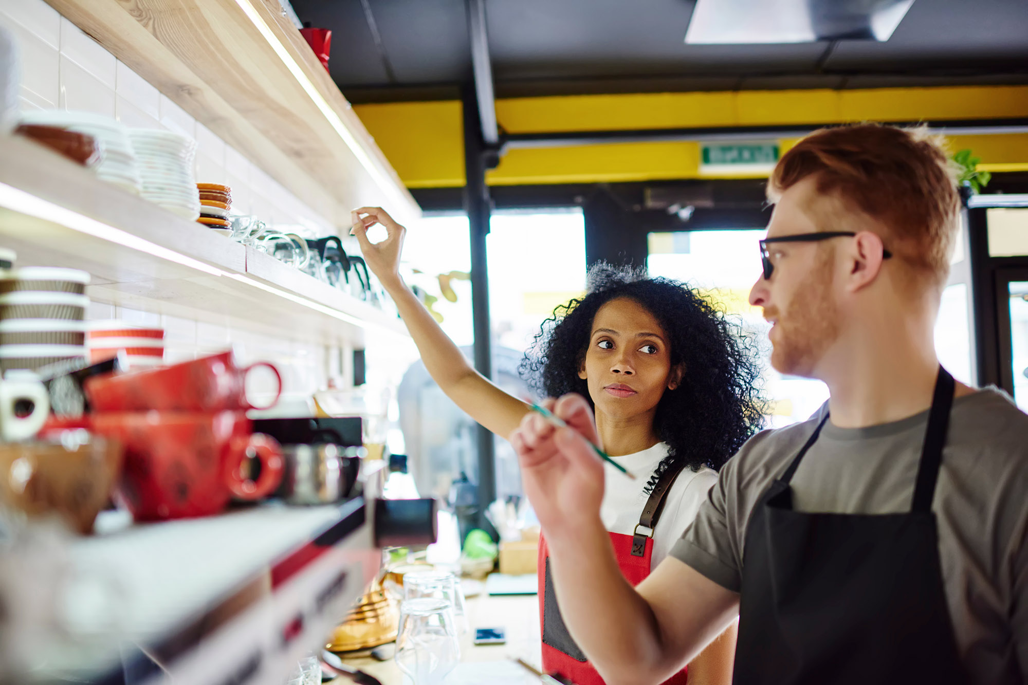 Two restaurant employees discuss inventory while looking at a shelf