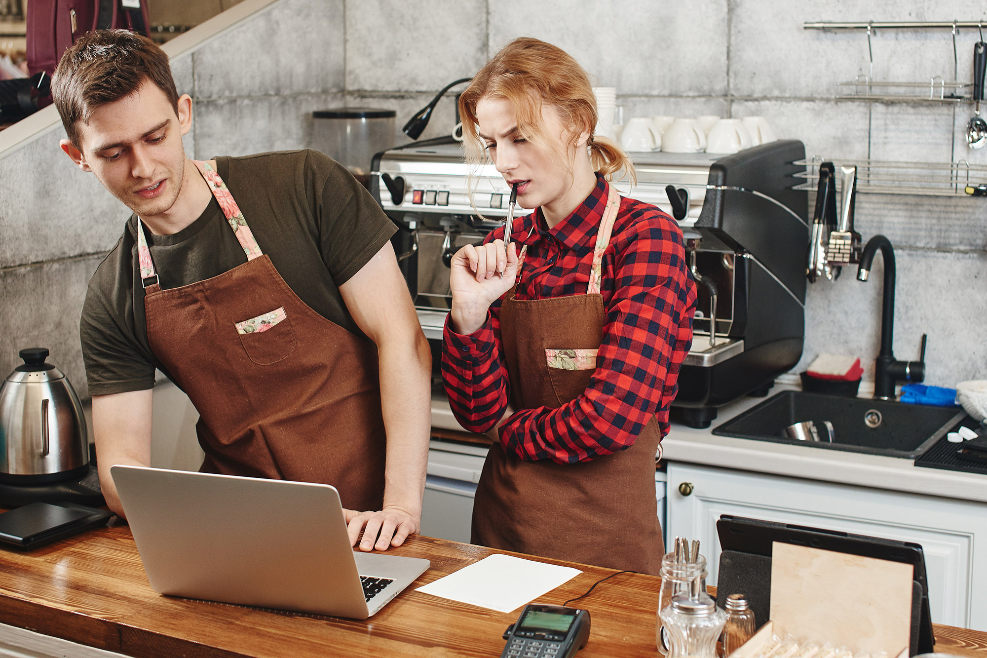 Two restaurant employees share a computer and discuss inventory
