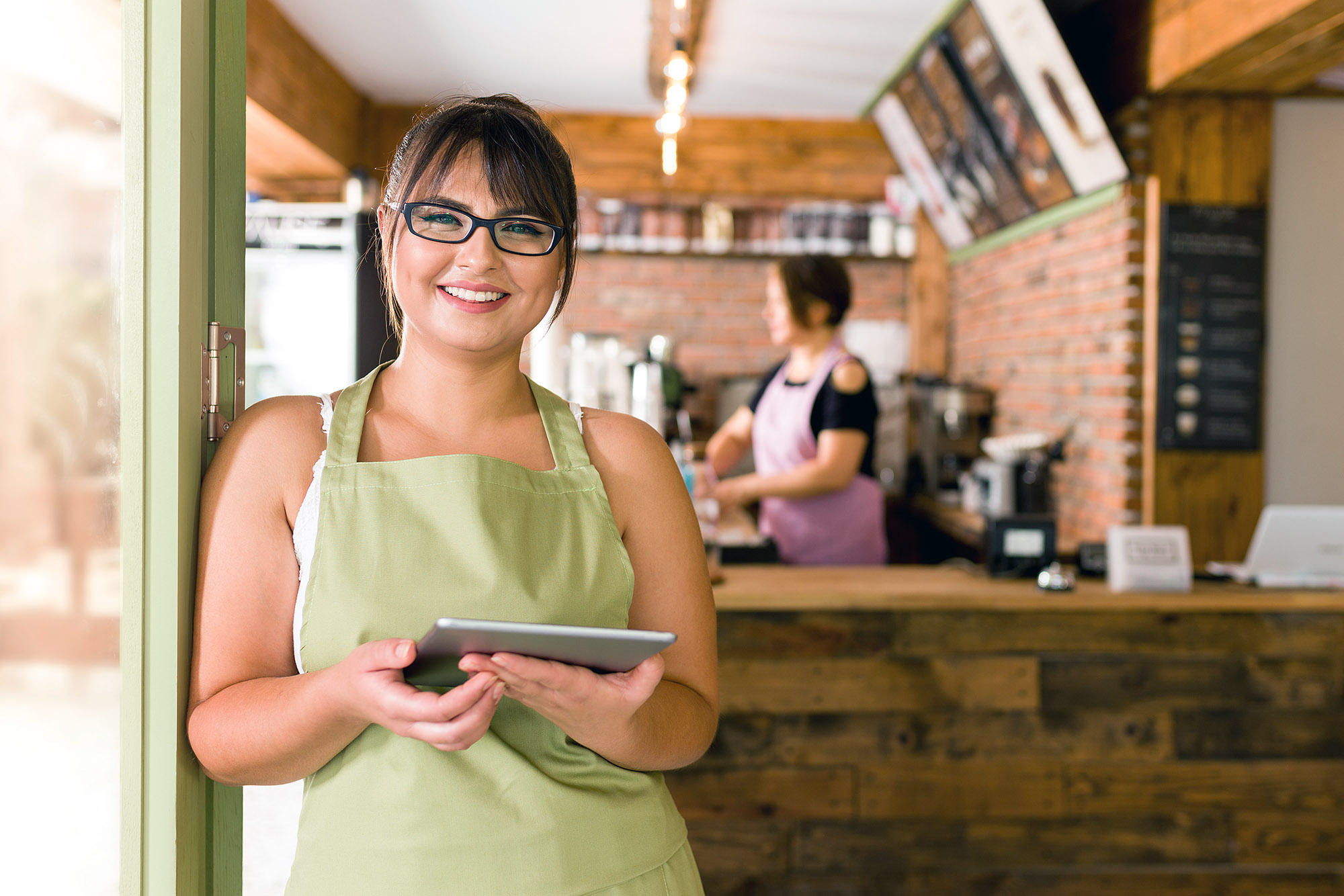 A happy restaurant owner stands at the door of her shop holding a tablet and smiles
