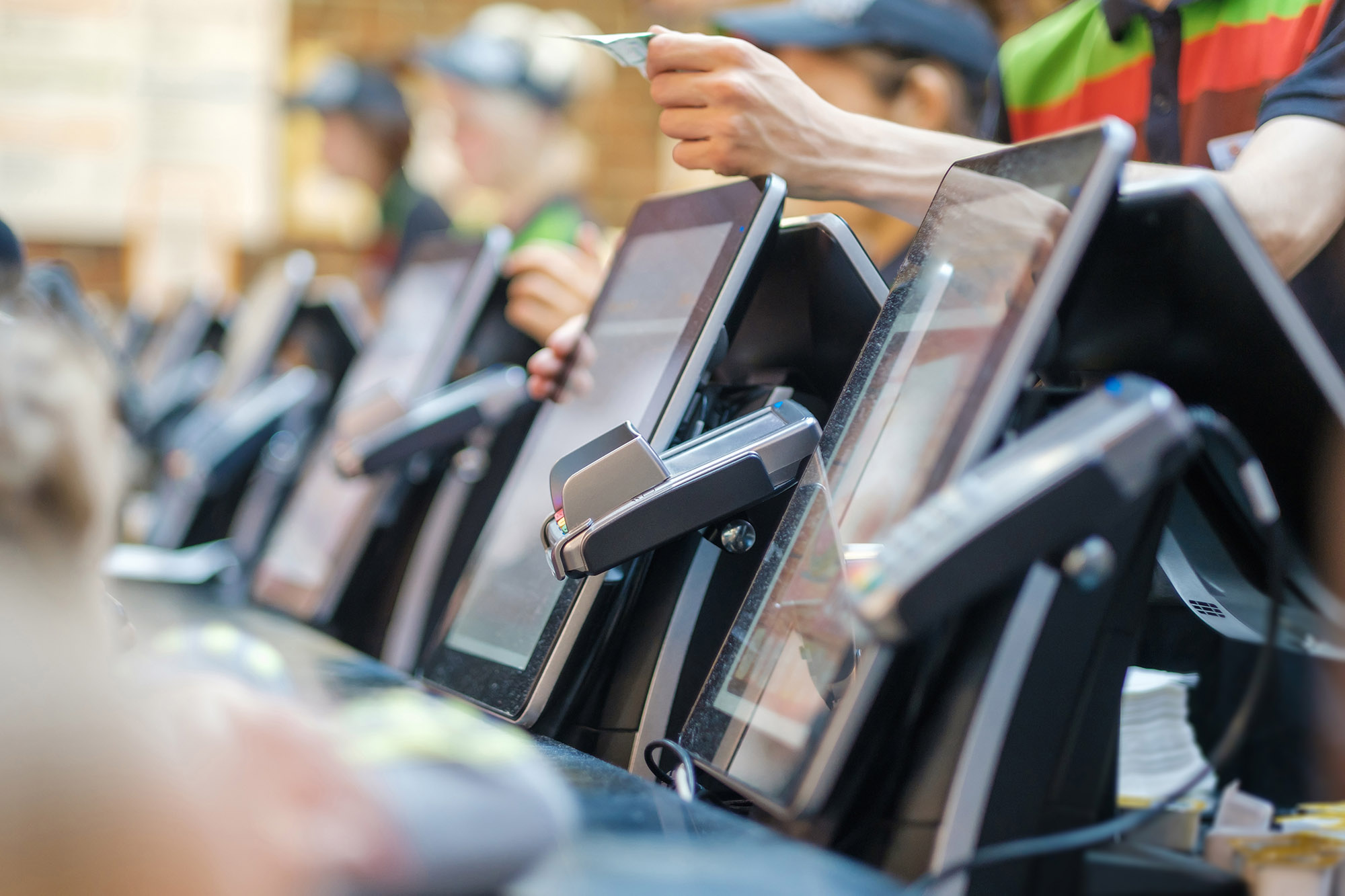 A row of POS machines at the front counter of a fast food restaurant
